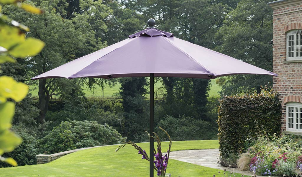 The 2.3m Push-Up Parasol in Amethyst in front of a lawn.