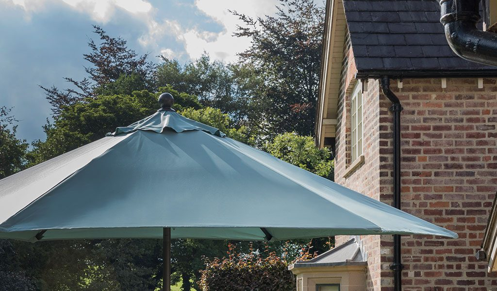 The 2.3m Push-Up Parasol in Aqua in front of a house.