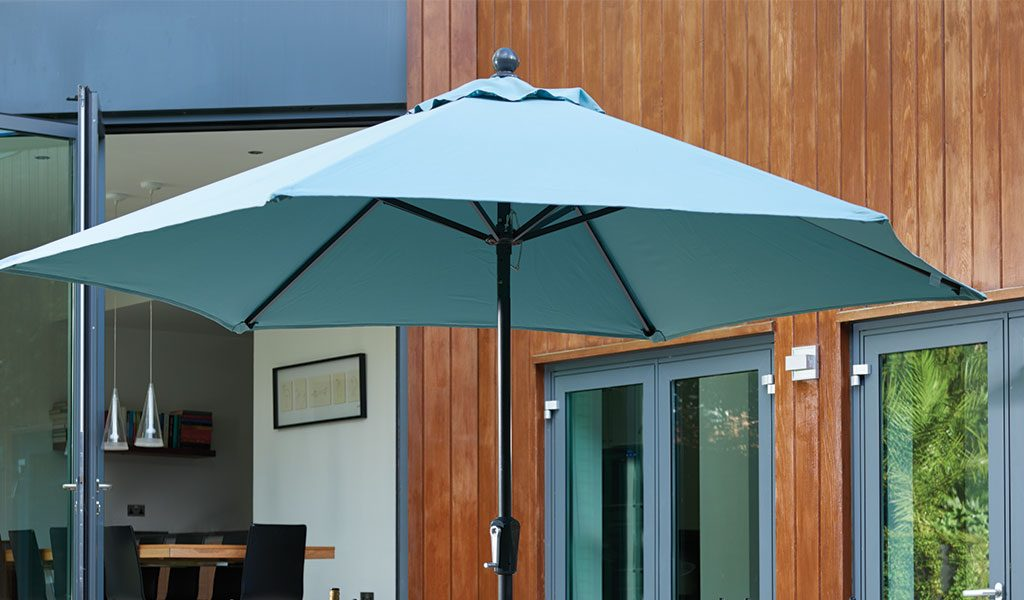 The 2.9m Push-Up Parasol in Aqua in front of a house.