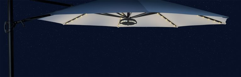 The 3.3m Free Arm Parasol with LED lights in front of a dark night sky.