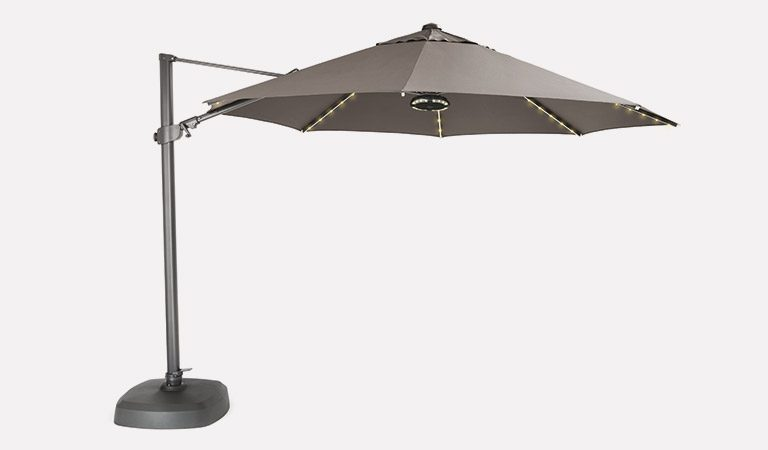 The 3.5m Free Arm Parasol with LED lighting and Wireless Speaker switched on with a taupe canopy, on a grey background.