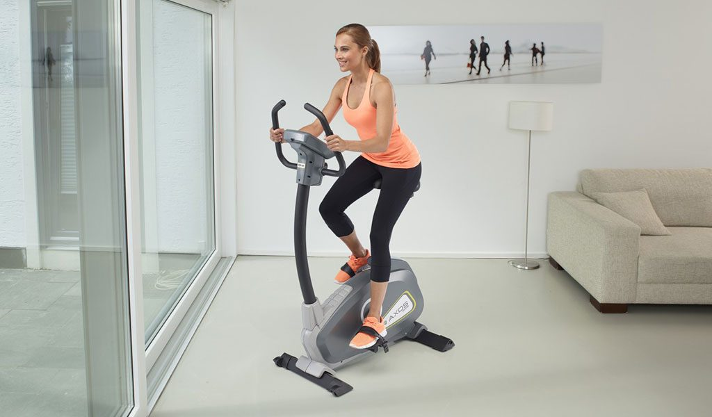 Woman exercising indoors on the Cycle P Exercise Bike from KETTLER's fitness range.