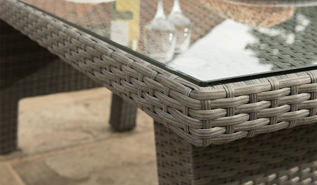 Detail of the Caleta Glass Top Table from KETTLER's Casual Dining garden furniture range on a patio.