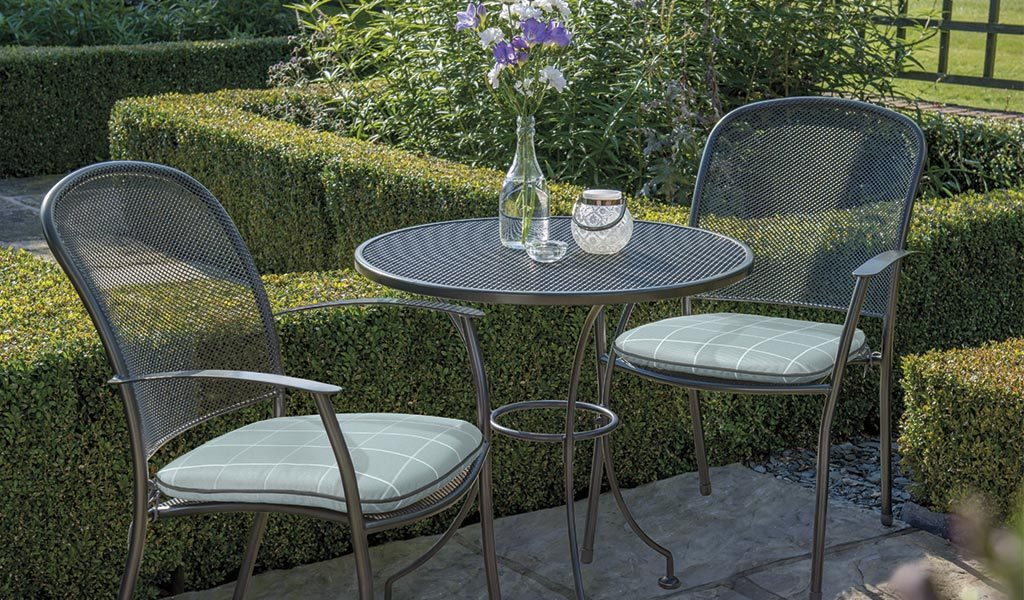 Two Caredo Chairs with aqua check seat pads and 70cm Mesh Table from KETTLER's Classic metal garden furniture range on a patio.