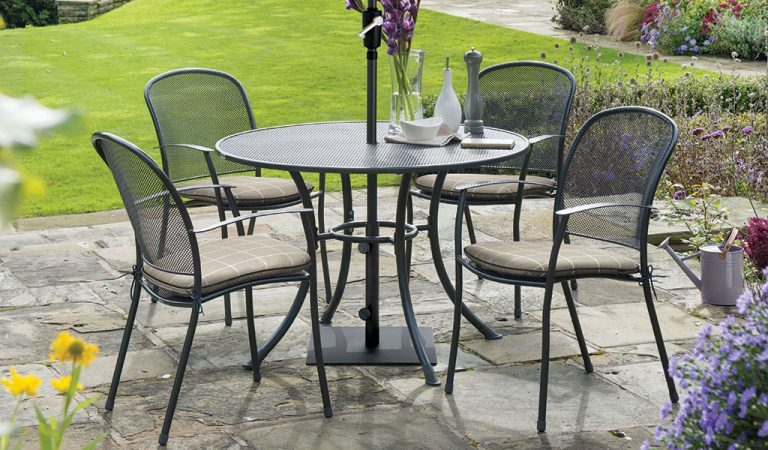 Caredo 4 Seater Dining Set with Stone check seat pads from KETTLER's Classic metal garden furniture range on a patio.