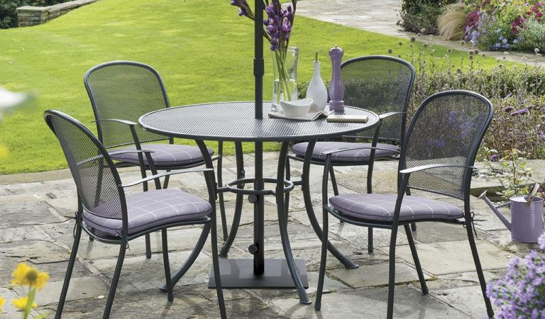 Caredo 4 Seater Dining Set with wisteria check seat pads from KETTLER's Classic metal garden furniture range on a patio.