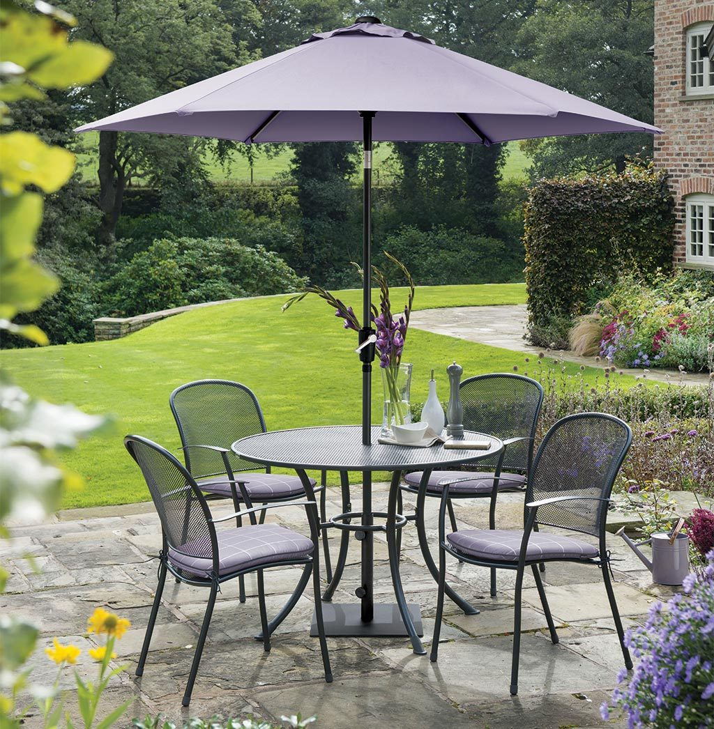 Caredo 4 Seater Dining Set with Wisteria Check coloured cushion and parasol.