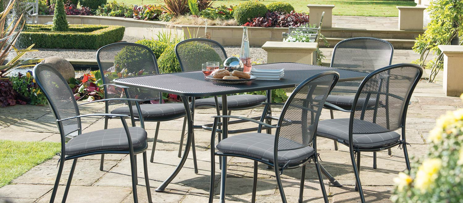 Caredo 6 Seater Dining Set with Slate Check seat pads from KETTLER's Classic range in a garden.