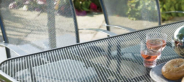 Blurred detail of the Caredo Chair and mesh table from KETTLER's Classic garden furniture range