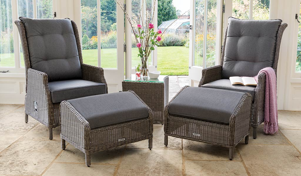 Classic Recliner with Footstool from Kettler wicker garden furniture in a conservatory.