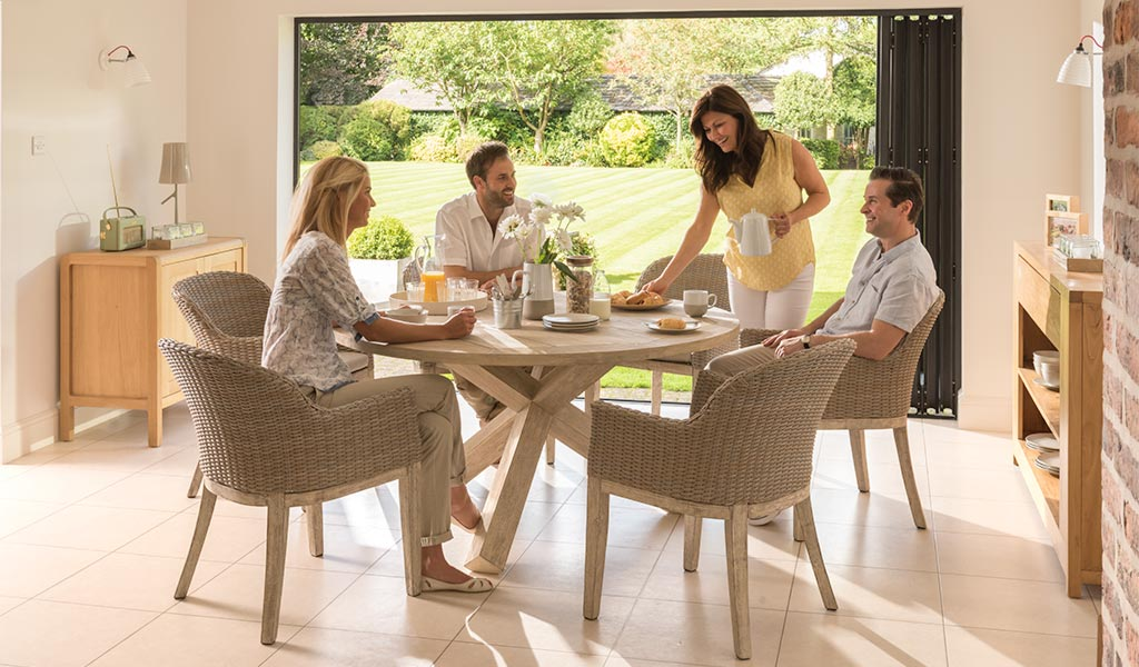 Two couples dining on the Cora round back Dining Set from KETTLER's Elegance range in a conservatory