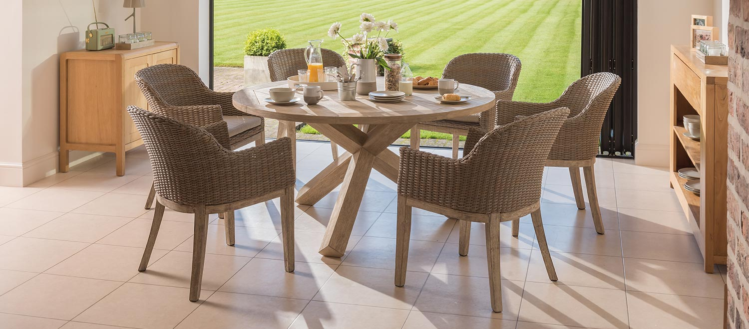 The KETTLER Cora Round Back Chair with the Cora Round Garden Table in a conservatory