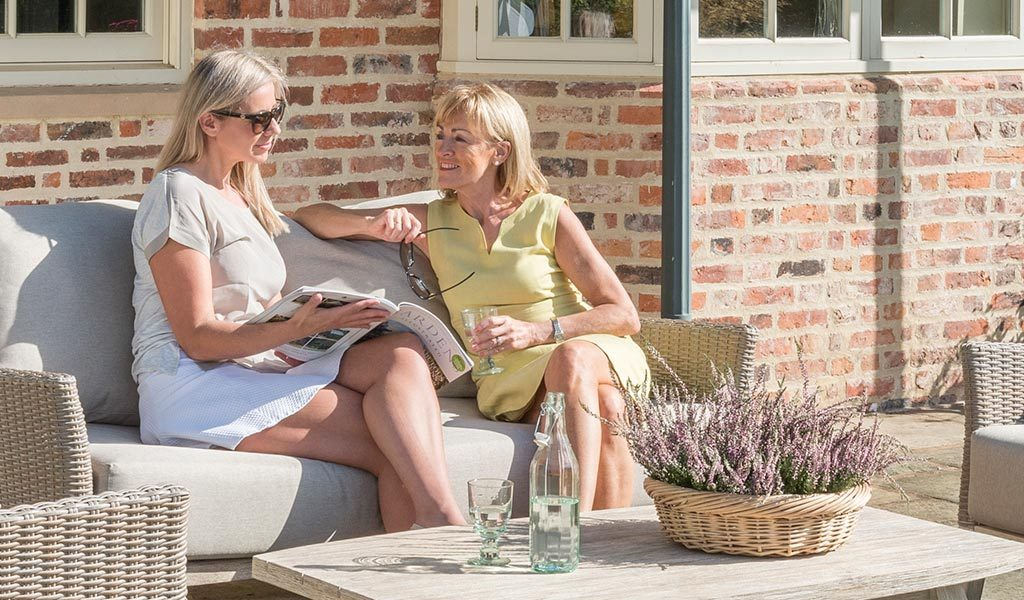 Two women lounging on the Cora Lounge Set from KETTLER's Elegance range on a patio