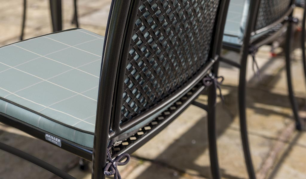 Detail of two Cortona Side Chairs with Aqua Check Seat Pads.