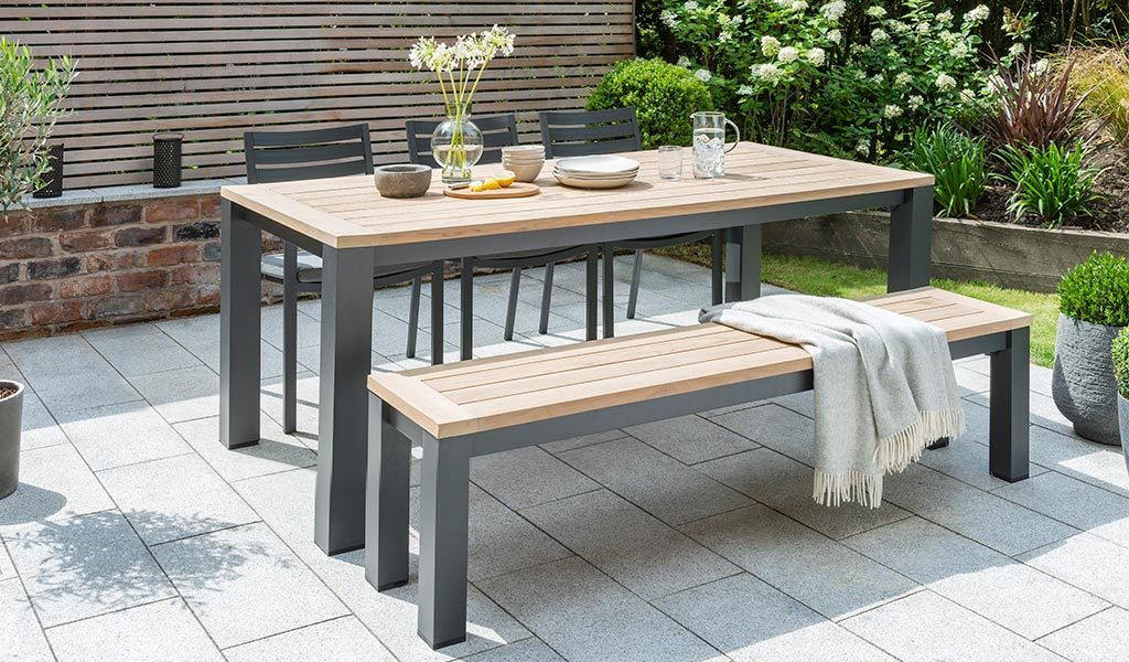 Elba Dining Set containing garden bench, chair and table on a patio.