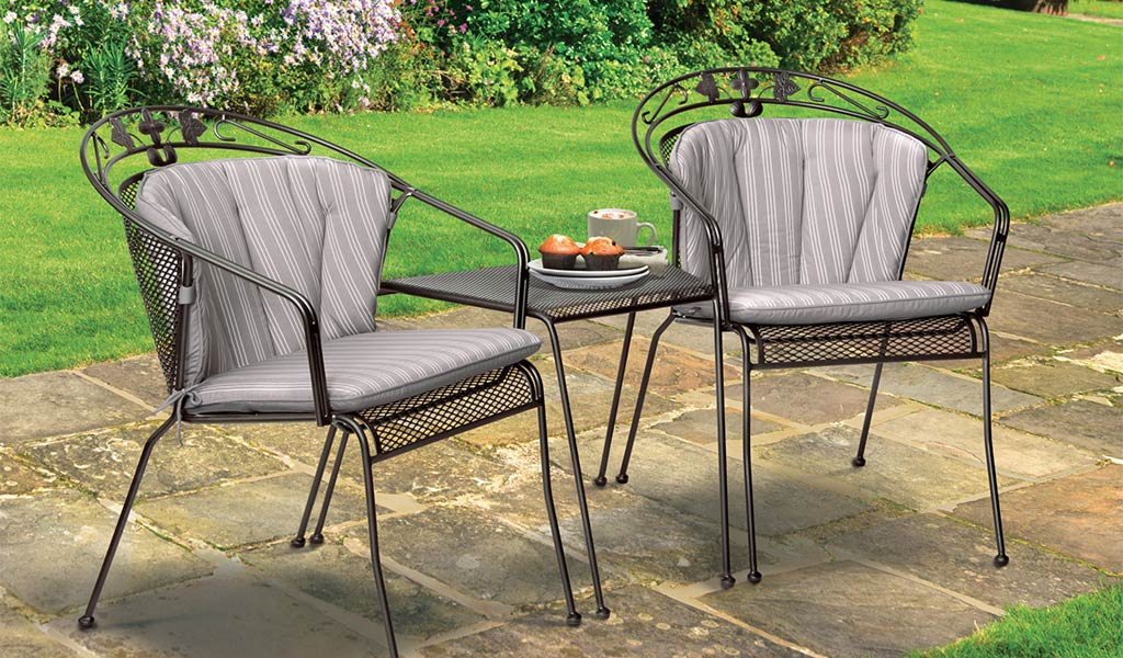 Henley Round Back Dining Set in Iron Grey from the KETTLER at John Lewis garden furniture range on a patio.