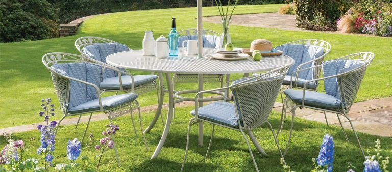 6 John Lewis Henley Round Back Chairs with Henley Round Back Chair Cushions - Pacific Blue Stripe/Plain going around a Henley Mesh Table - Mellow Mocha in a garden.