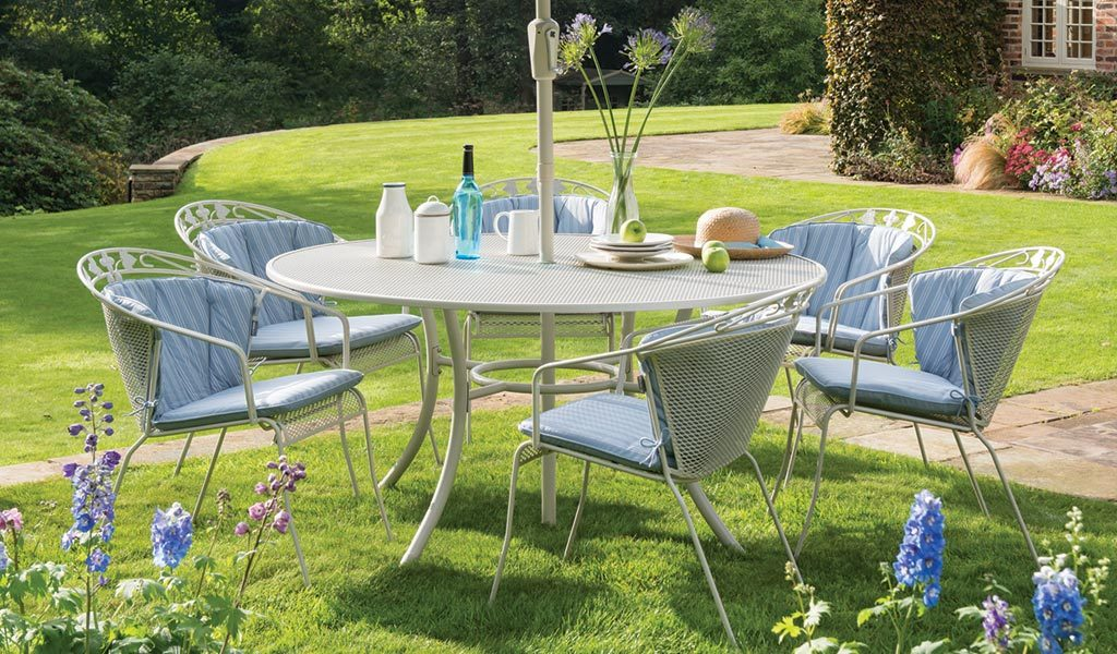 Henley Round Back Dining Set in Mellow Mocha from the KETTLER at John Lewis garden furniture range on a lawn.