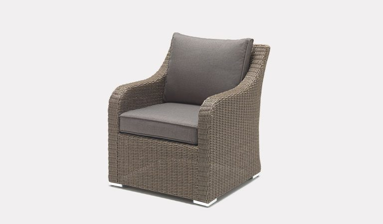 The Madrid Armchair in rattan from KETTLER's Casual Dining Garden furniture range on a grey background.