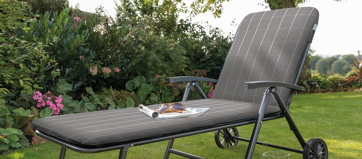 The Novero Lounger with Slate Check coloured cushions on a lawn in the garden.