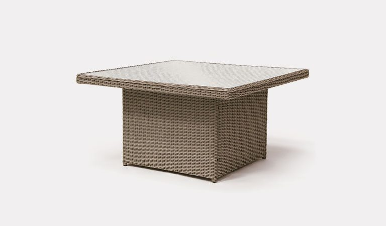 Palma 120cm Glass Top table in rattan from KETTLER's Casual Dining Garden furniture range on a grey background.