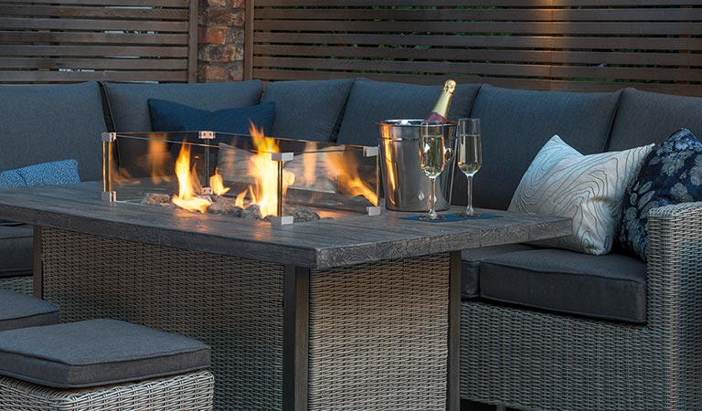 Close up of a lit Palma Fire Pit Table from the Kettler Palma garden furniture range, in a garden.