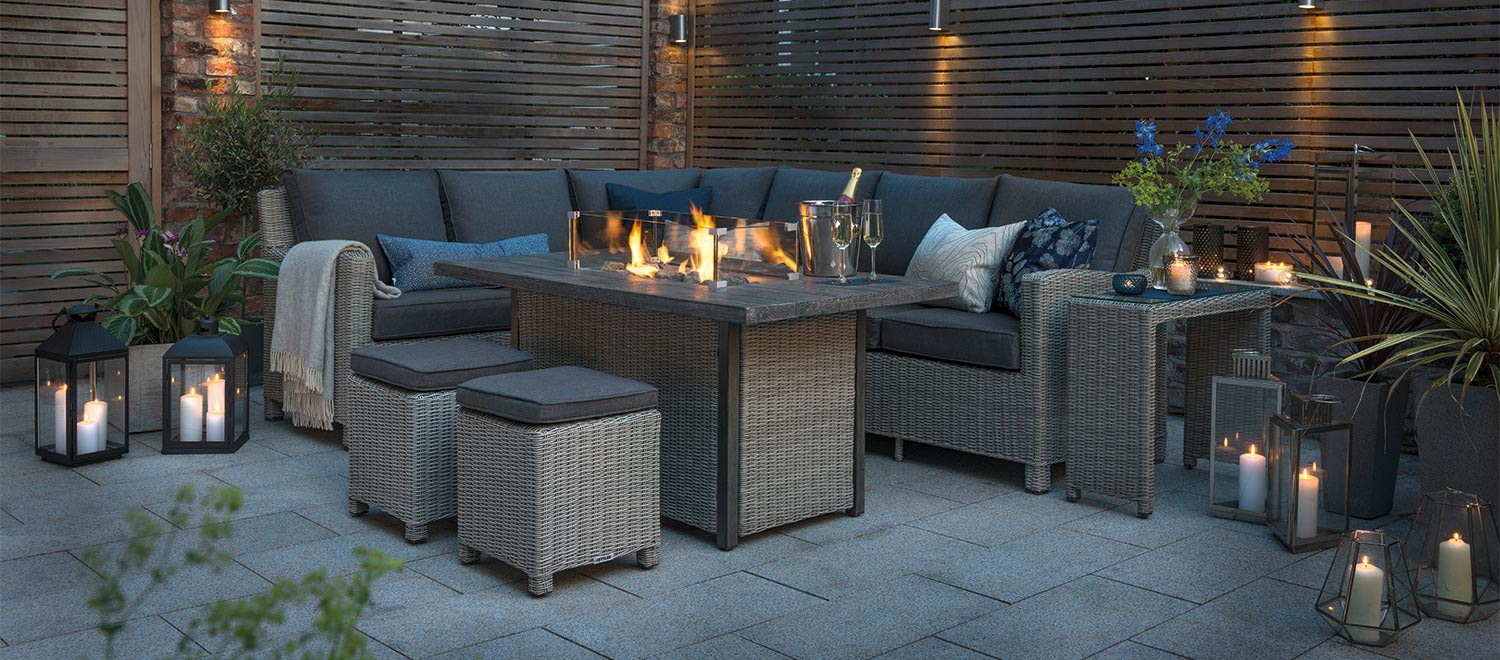 The Palma Corner Sofa with a lit Palma Fire Pit Table on a patio at night.