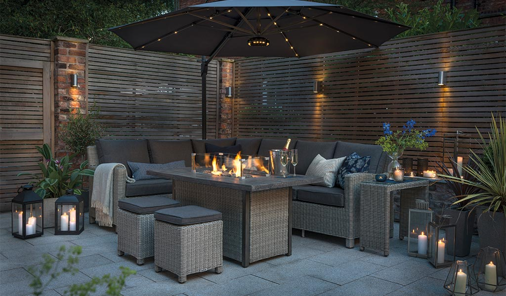 The Palma Corner Sofa with a lit Palma Fire Pit Table and 3.5m Free Arm Parasol with LED Lighting and Wireless Speaker on a patio at night.