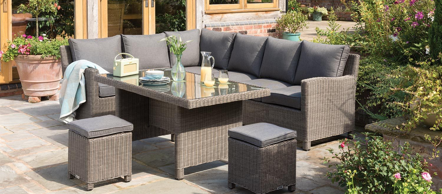 The Kettler Palma Corner Sofa in rattan with a Palma Glass Top Table in a garden.