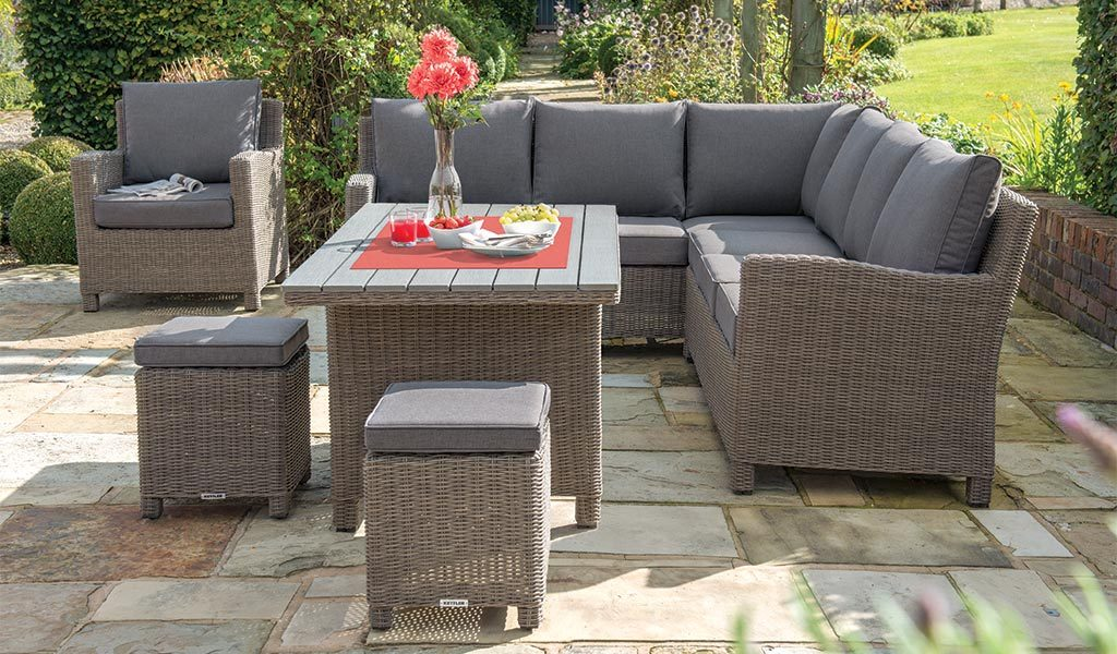 Palma Corner Set in rattan with dark oak slat top Table from KETTLER's Casual Dining range on a patio.