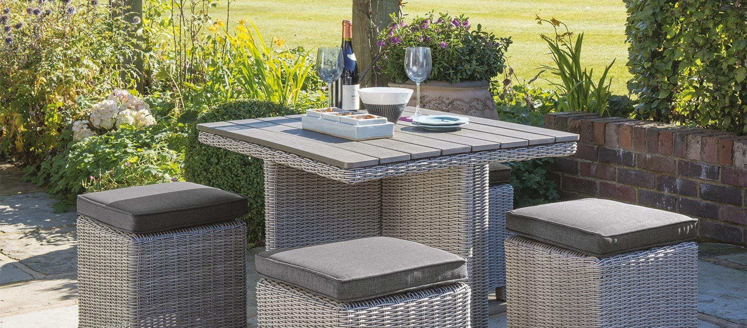 Palma Cube Set garden furniture in white wash wicker from KETTLER's Casual Dining range on a patio.