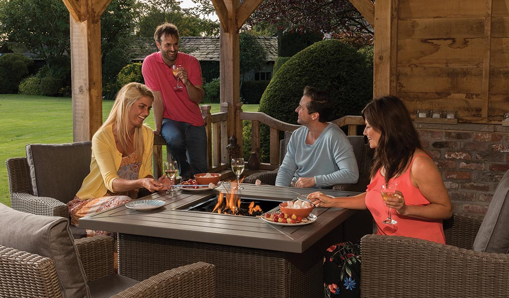 Two couples dining and having fun around the Palma Fire Pit Table from KETTLER's Casual Dining garden furniture range in a bungalow