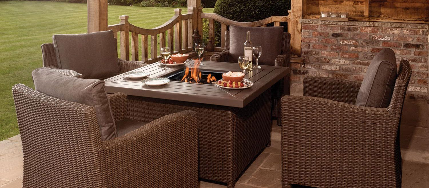 Palma Fire Pit Table with Armchairs in rattan from KETTLER's Casual Dining range on a patio in front of a house