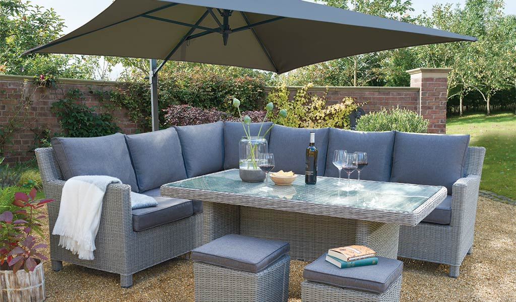 Palma Corner Set in white wash with Glass Top Table and 2.5m Free Arm parasol from KETTLER's Casual Dining range on a patio in front of a house