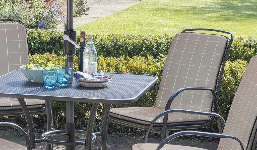 Closeup of the Savita 4 Seater Dining Set with Slate cushions from KETTLER's Classic range on a patio