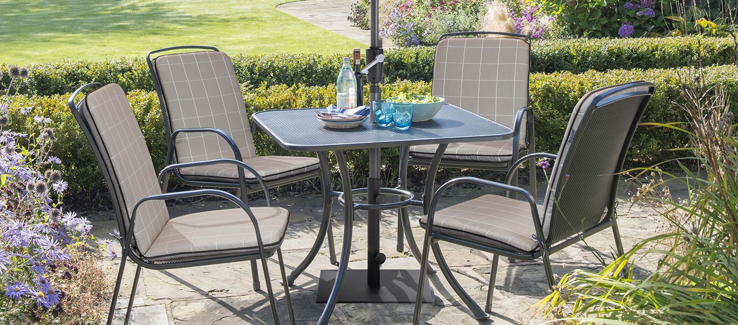 Savita 4 Seater Dining Set with Slate cushions from KETTLER's Classic range on a patio