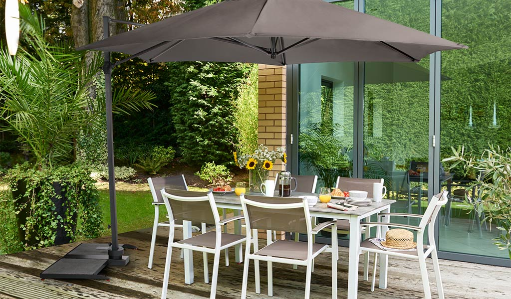Treviso Dining Set in Taupe/Hessian with 3.5m Free Arm Parasol from KETTLER's Classic garden furniture range on a patio.