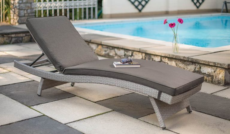 The universal wicker Lounger in white wash from KETTLER's Classic garden furniture range in front of a swimming pool.