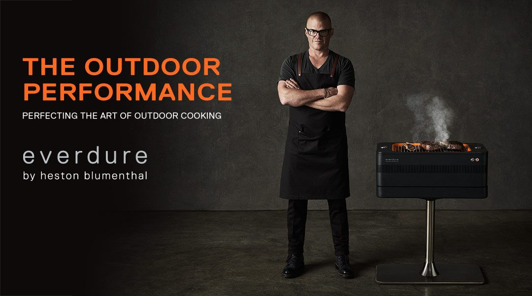 Heston Blumenthal stood next to an Everdure Fusion charcoal BBQ.