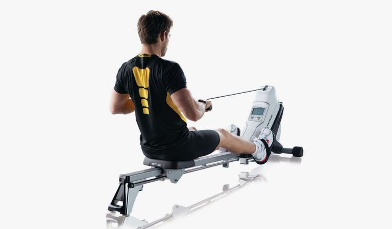 Man exercising on the Coach M Rowing Machine from KETTLER's fitness range on a grey background.