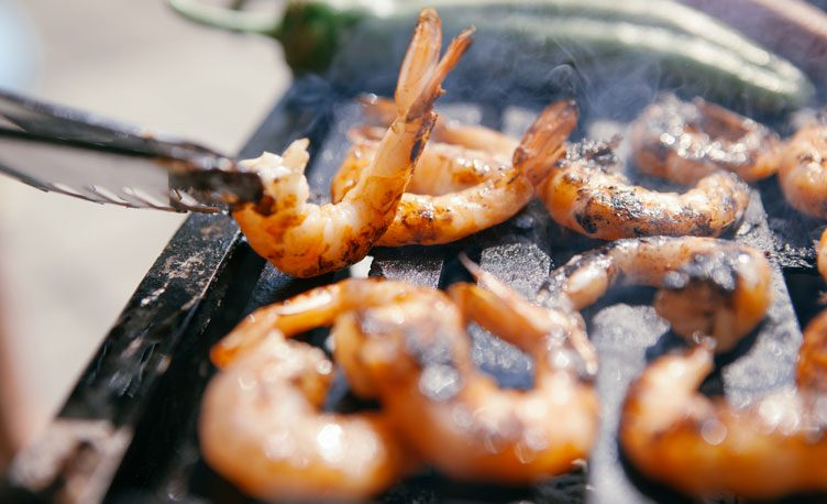 .Chargirlled tiger prawns sizzling on a barbecue.