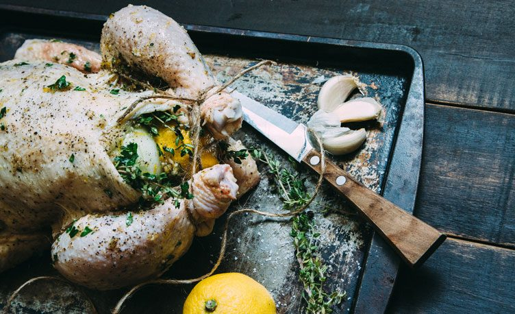 Filled chicken with herb and a lemon lying on a baking tray.