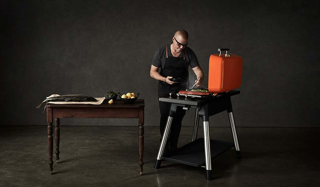 Heston Blumenthal cooking fish on an Orange FURNACE gas BBQ in front of a black background.