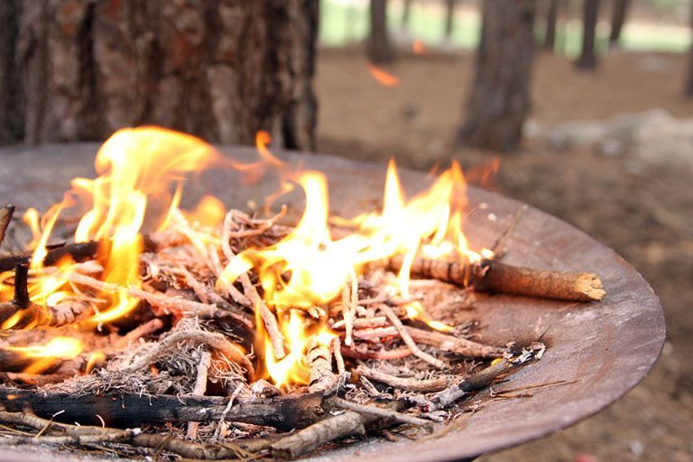 Metal fire pit bowl with burning twigs in it, in wooded area