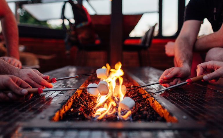 Close-up of marshmallows being roasted over a fire pit table