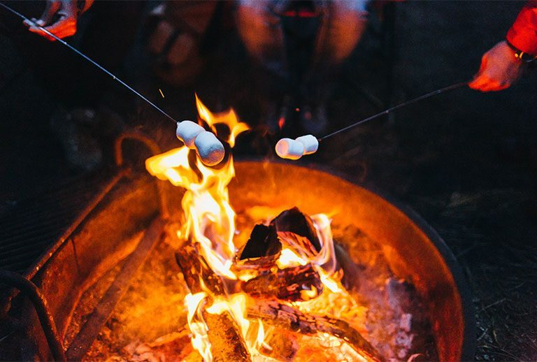 Flaming fire pit with two marshmallows.