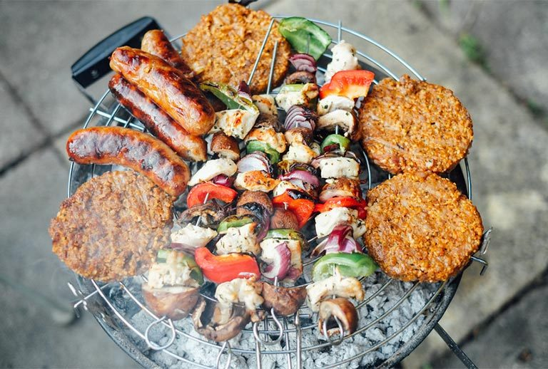 Burger, sausages and kebabs sizzling on a barbecue.