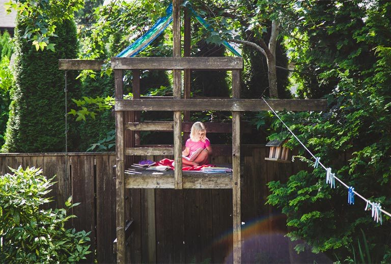 Blonde girl reading in a wooden treehouse.