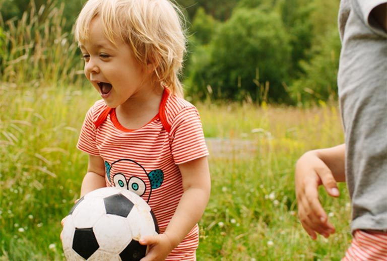 Two children playing football in a field.