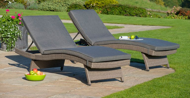 Two Kettler rattan weave sun loungers in garden